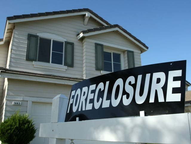 A foreclosure sign sits in front of a home for sale n Stockton, Calif. The city was hit hard by the housing bust more than seven years ago and is among the former boomtowns that remain a long way from recovery.