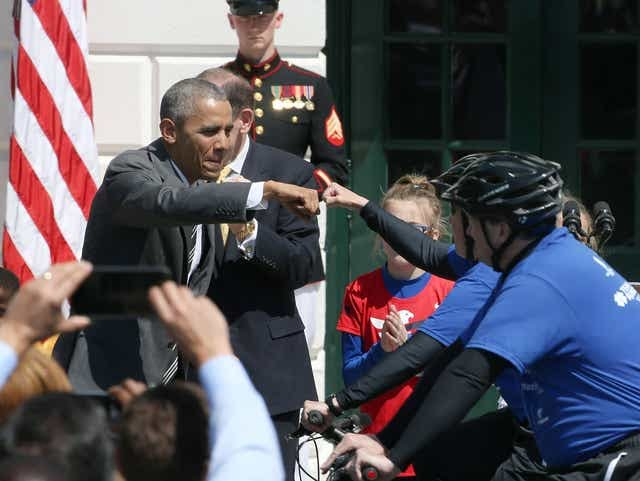 President Obama fist pumps a rider after signaling the start of the Wounded Warrior Ride, on the South Lawn of the White House Thursday.