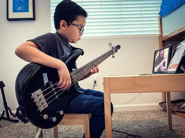 A student participates in a remote lesson through School of Rock.