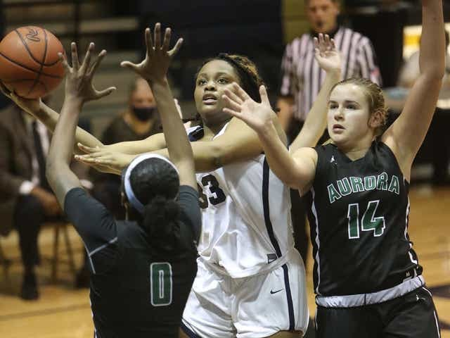 Archbishop Hoban's Adrena Gordon, center, tries to get a shot off between Aurora's Shyanne Sellers, left, and Ava Ryncarz during the Knights' 74-56 win in a Division I district semifinal Tuesday night in Akron. [Karen Schiely/Beacon Journal]