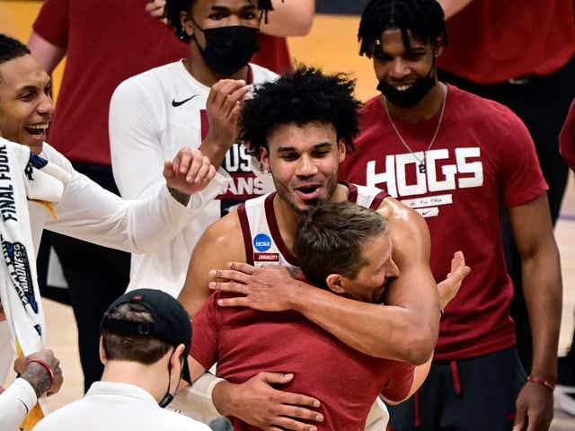 Justin Smith embraces coach Eric Musselman after Arkansas defeated Texas Tech in the second round of the 2021 NCAA Tournament at Hinkle Fieldhouse.